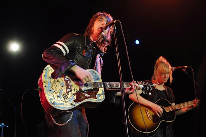 A man and a woman playing guitars onstage.