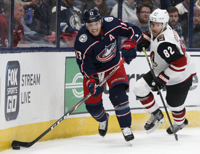 Columbus Blue Jackets' Cam Atkinson, left, clears the puck as Arizona Coyotes' Jordan Oesterle defends during the second period of an NHL hockey game Tuesday, Dec. 3, 2019, in Columbus, Ohio. (AP Photo/Jay LaPrete)