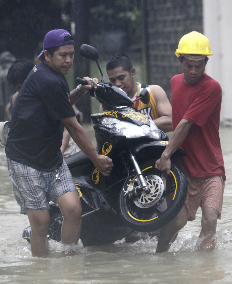 Residents carry a motorcycle across a flooded street in Marikina, east of Manila, Philippines on Tuesday, Aug. 7, 2012. Torrential rains pounding the Philippine capital on Tuesday paralyzed traffic as waist-deep floods triggered evacuations of tens of thousands of residents and the government suspended work in offices and schools. (AP Photo/John Javellana)