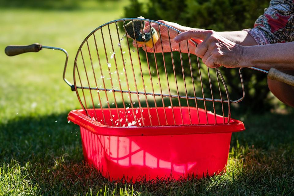 """<p>Even if you take impeccable care of your grill with regular cleanings, if it's been out of regular use, it's a good idea to begin by removing the cobwebs and cleaning the grates. Remove the grates and soak them in soapy water to start.</p> <p>The editorial team at <a href=""""https://amazingribs.com/?referrer=yahoo&category=beauty_food&include_utm=1&utm_medium=referral&utm_source=yahoo&utm_campaign=feed"""" rel=""""nofollow noopener"""" target=""""_blank"""" data-ylk=""""slk:AmazingRibs.com recommends"""" class=""""link rapid-noclick-resp"""">AmazingRibs.com recommends</a> removing rust spots by scrubbing hard with a grill brush or steel wool. Then treat your grates as you would a cast iron pan and season them by rubbing an oil-soaked paper towel over the grates. Once you're finished, heat the grill to high and re-apply vegetable oil to the grates with paper towels attached to tongs. This process creates a layer of lubricant on the grill grates, preventing sticking and rusting. They suggest applying oil like this before you grill every time to keep the grates well-seasoned, <a href=""""https://www.thedailymeal.com/cook/cast-iron-pan-mistakes?referrer=yahoo&category=beauty_food&include_utm=1&utm_medium=referral&utm_source=yahoo&utm_campaign=feed"""" rel=""""nofollow noopener"""" target=""""_blank"""" data-ylk=""""slk:similar to a cast iron pan"""" class=""""link rapid-noclick-resp"""">similar to a cast iron pan</a>. While you're at it, you might as well clean the outside of the grill and lubricate the knobs if they feel sticky.</p>"""