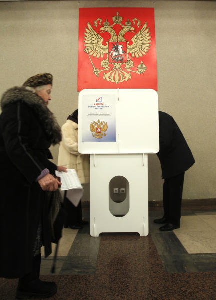 A Russian woman walks to cast her ballot at a polling station in Moscow on Sunday, March 4, 2012. Polling stations have opened across Russia's vast expanse for the presidential election widely expected to return Vladimir Putin to the Kremlin. (AP Photo/Misha Japaridze)