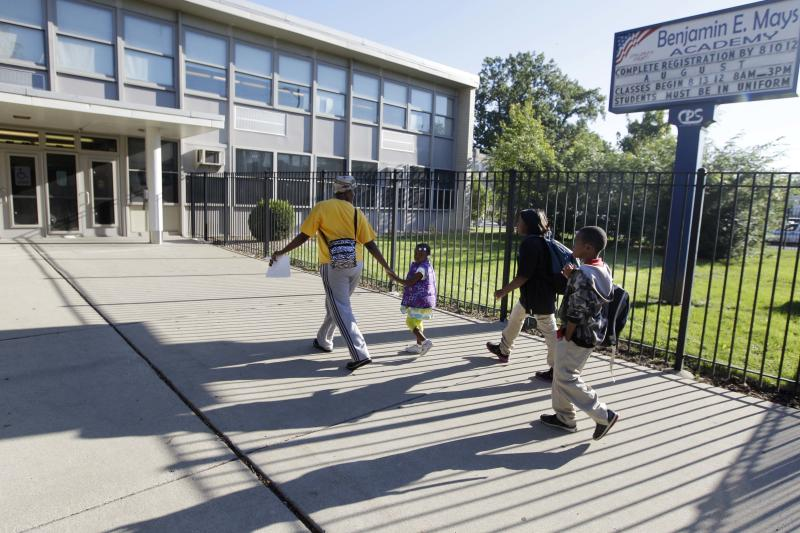 Parents drop their children off at Benjamin E. Mays Academy, one of the few schools open for a half day during the first day of a Chicago teachers strike, Monday, Sept. 10, 2012, in Chicago. Thousands of teachers walked off the job in the nation's third-largest school district for the first time in 25 years after union leaders announced they were far from resolving a contract dispute with school district officials. (AP Photo/M. Spencer Green)