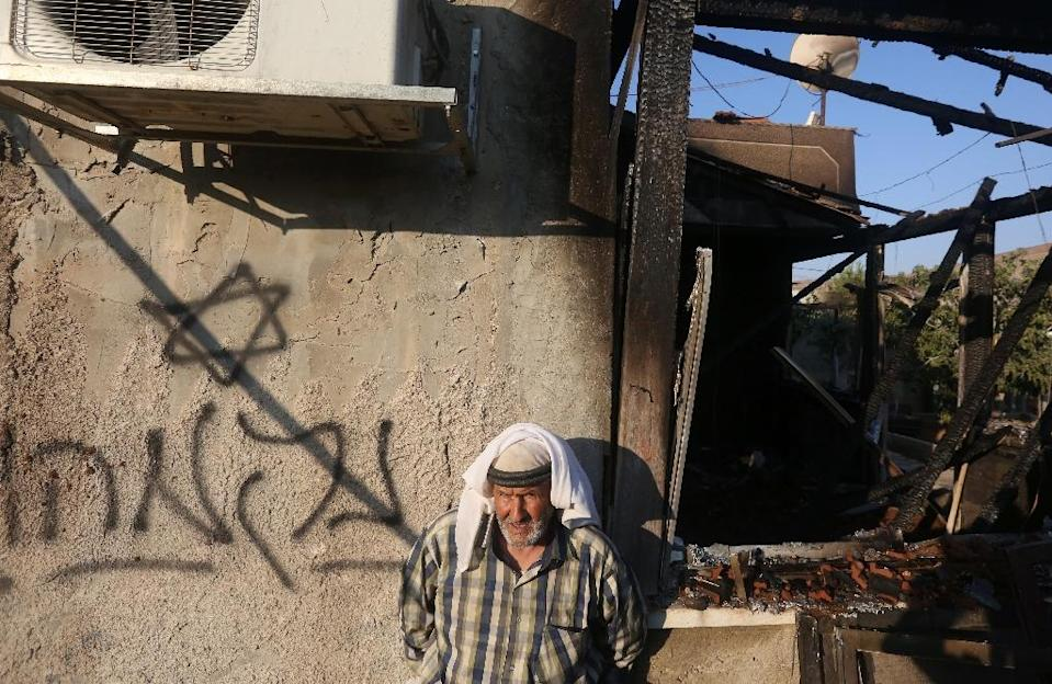 """A Palestinian man stands next to graffiti reading in Hebrew """"Revenge"""" as he looks at the damage after a house was set on fire by Jewish settlers in the West Bank village of Duma on July 31, 2015 (AFP Photo/Jaafar Ashtiyeh)"""