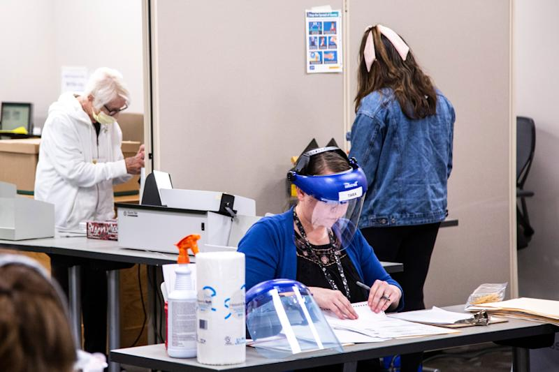 Workers wearing face shields and masks sort mail-in primary election ballots June 1 at the Johnson County Health and Human Services building in Iowa City, Iowa.