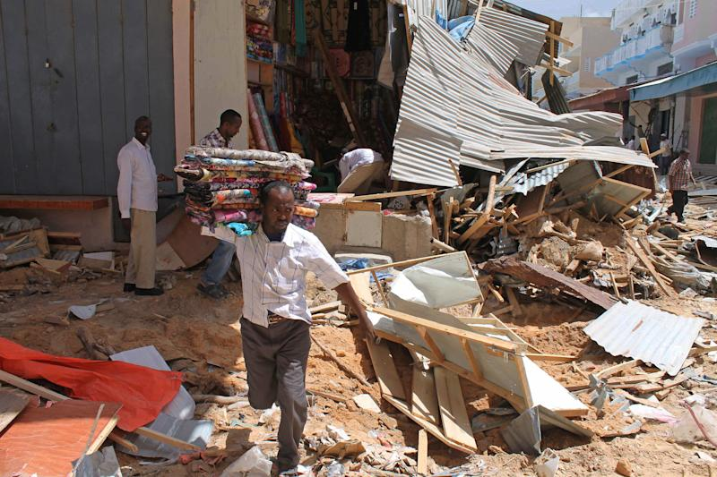 In this photo of Monday April 30 2012, Somalis traders hurriedly remove their goods from their illegal kiosks and business sites after demolition in Mogadishu's Bakara market in Mogadishu Somalia . Bulldozers protected by government troops are demolishing small kiosks along a street in Mogadishu's largest market.  The bulldozing operation taking place is a city-backed effort to help clean up Mogadishu and create space in a a crowded market throughway. For the affected traders, there is a certain irony in the government initiative. For years Somalis have lamented the fact that their city had no government. Now that life is returning to a semblance of normal in a city that has endured 20 years of conflict, the businessmen on the receiving end of the clean-up plan are voicing reservations about city management.(AP Photo/Farah Abdi Warsameh)