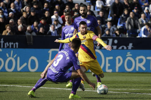 Barcelona's Lionel Messi, center, attempts a shot at goal in front of Leganes' Unai Bustinza during a Spanish La Liga soccer match between Leganes and FC Barcelona at the Butarque stadium in Madrid, Spain, Saturday Nov. 23, 2019. (AP Photo/Paul White)