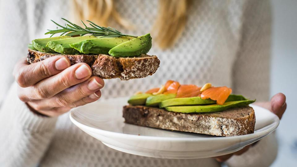 millennial woman eating avocado toast saving her money