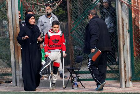 """Nour Eldin Ahmed, 12, a member of """"Miracle Team"""", a soccer team made up of one-legged, crutch-bearing soccer players, arrives with his mother at a training session at El Salam club on the outskirts of Cairo, Egypt December 29, 2017. REUTERS/Amr Abdallah Dalsh"""