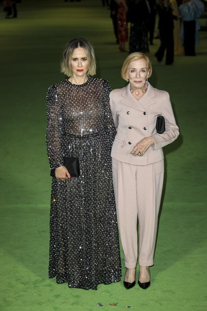 A woman in a black sequined dress next to a woman in a beige pantsuit on the green carpet