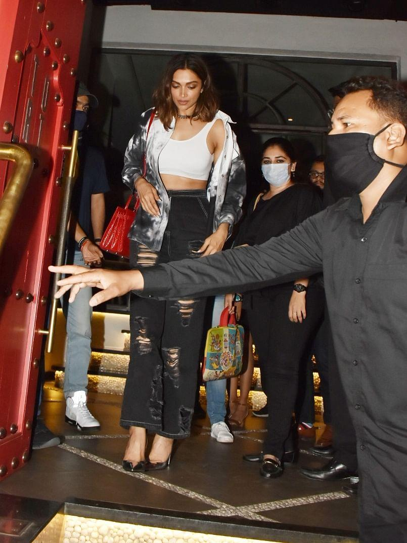 <p>Deepika chose a black distressed jeans, a white top, and a shrug for the occasion.</p>
