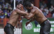 Wrestlers Ismail Koc, right, and Faruk Akkoyun compete during the semi-final of the 660th instalment of the annual Historic Kirkpinar Oil Wrestling championship, in Edirne, northwestern Turkey, Sunday, July 11, 2021.Thousands of Turkish wrestling fans flocked to the country's Greek border province to watch the championship of the sport that dates to the 14th century, after last year's contest was cancelled due to the coronavirus pandemic. The festival, one of the world's oldest wrestling events, was listed as an intangible cultural heritage event by UNESCO in 2010. (AP Photo/Emrah Gurel)