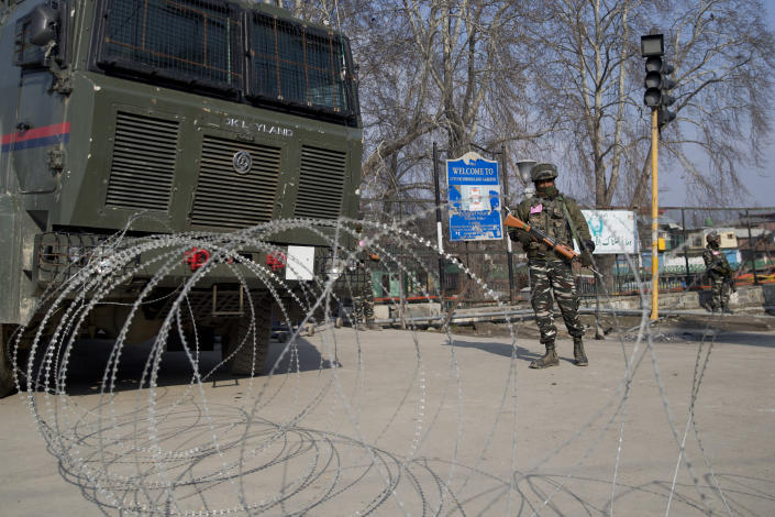 Indian paramilitary soldiers are seen near a barbed wire at a checkpoint during a strike in Srinagar, Indian controlled Kashmir, Sunday, Feb. 3, 2019. India's prime minster is in disputed Kashmir for a daylong visit Sunday to review development work as separatists fighting Indian rule called for a shutdown in the Himalayan region. (AP Photo/Dar Yasin)