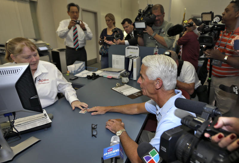 FILE - In this Thursday, Dec. 13, 2012 file photo, former Republican Florida Governor Charlie Crist, right, hands his drivers license to Piniellas County Supervisor of Elections worker Janet Hamilton in St. Petersburg, Fla. Crist officially switched his party affiliation to the Democrat party. Three years after leaving the Florida governor's mansion and losing a U.S. Senate campaign, Charlie Crist is plotting a political comeback. The man who once identified himself as a Ronald Reagan Republican is gearing up for another gubernatorial bid as a Barack Obama Democrat. (AP Photo/Chris O'Meara)