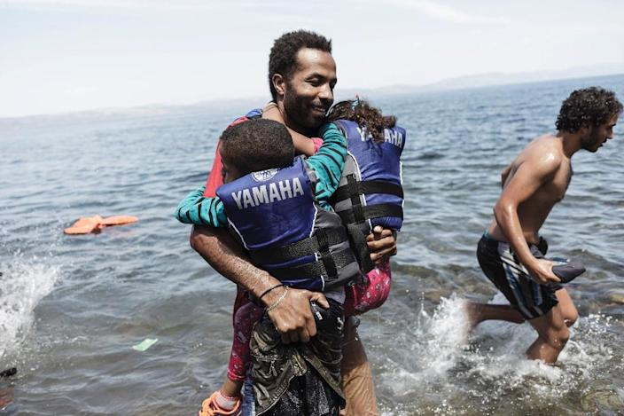 A migrant carries his two children as he gets off an inflatable boat after arriving on the Greek island of Lesbos after crossing the Aegean sea from Turkey on August 14, 2015 (AFP Photo/Achilleas Zavallis)