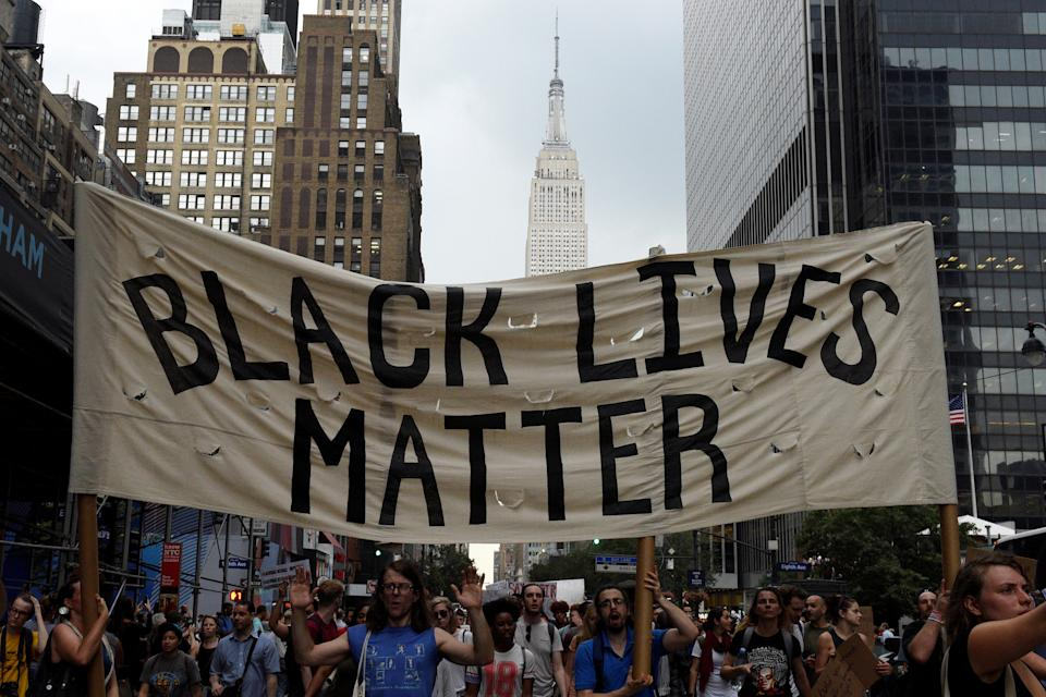 People take part in a protest against the killings of Alton Sterling and Philando Castile during a march through Manhattan, with the Empire State Building seen in the background, in New York July 7, 2016. REUTERS/Darren Ornitz