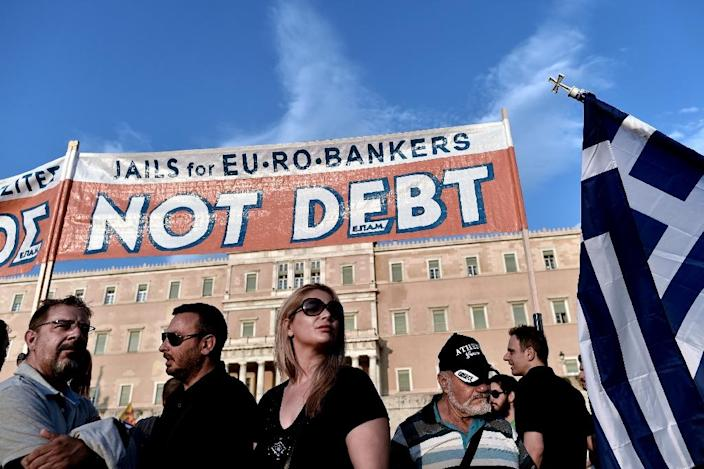 Prostestors stand below a banner in reference to the referendum on bailout conditions set by the country's creditors, during a demonstration in front of the Greek parliament in Athens on June 29, 2015 (AFP Photo/Aris Messinis)