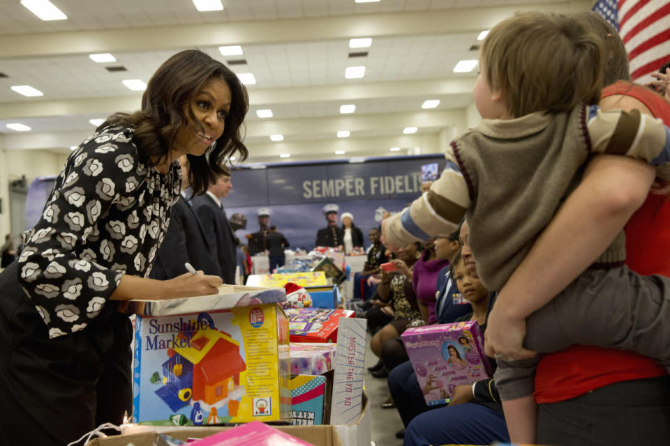 <p>First lady Michelle Obama, wearing a black and white paisly print blouse, greets one-year-old William Gettle and his mother Kelsey Gettle at a Toys for Tots event held by the Marine Corps Bolling Air Force Base in Washington, DC. <i>Photo: AP</i></p>