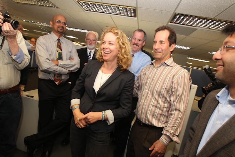 Los Angeles Times photographer Barbara Davidson, center, reporter Jeff Gottlieb, second from right, and reporter Ruben Vives, right, gather after hearing they had won a 2011 Pulitzer Prize. Davidson won the award for feature photography for a series of photographs on victims of gang violence in Los Angeles. Gottlieb and Vives won the award for their exposure of corruption in the small California city of Bell where officials tapped the treasury to pay themselves exorbitant salaries, resulting in arrests and reforms. (AP Photo/The Los Angeles Times, Christina House)