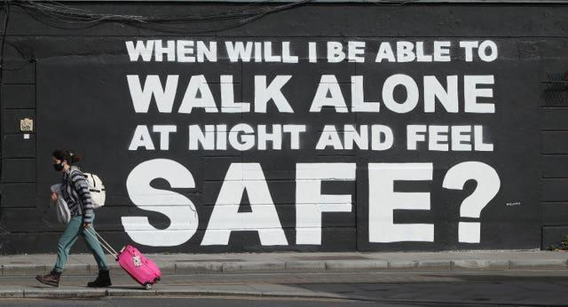 A member of the public walks past a mural asks: 'When will I be able to walk alone at night and feel safe?'