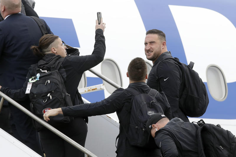 San Francisco 49ers offensive assistant Katie Sowers, left, holds up her phone next to offensive tackle Joe Staley, center right, as they depart for Miami from Mineta San Jose International Airport in San Jose, Calif., Sunday, Jan. 26, 2020. The 49ers will face the Kansas City Chiefs in Super Bowl 54. (AP Photo/Jeff Chiu)