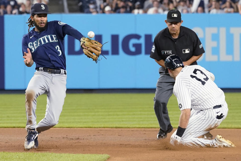 New York Yankees' Joey Gallo (13) slides into second with a double as Seattle Mariners shortstop J.P. Crawford (3) tries to catch the throw during the fourth inning of a baseball game Thursday, Aug. 5, 2021, in New York. (AP Photo/Mary Altaffer)