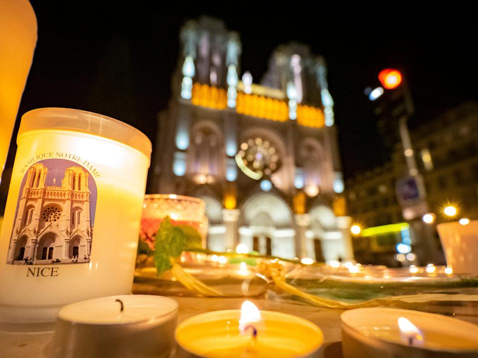 People pay tribute at night in front of Notre Dame Basilica on October 29, 2020 in Nice, France (Getty Images)