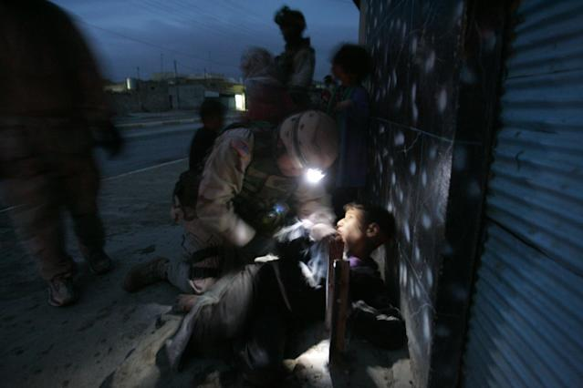 <p>An Iraqi boy is treated for a flesh wound in his back after U.S. Soldiers with the 1st Battalion, 5th Infantry Stryker Brigade Combat Team of the 25th Infantry Division out of Ft. Lewis, Washington killed his parents when their car approached soldiers, despite warning shots, during a dusk patrol January 18, 2005 in Tal Afar, Iraq. The car held an Iraqi family of which the mother and father were killed. According to the U.S. Army, six children in the in the car survived, one with a non-life threatening flesh wound. U.S. military said they are is investigating the incident. (Photo by Chris Hondros/Getty Images) </p>