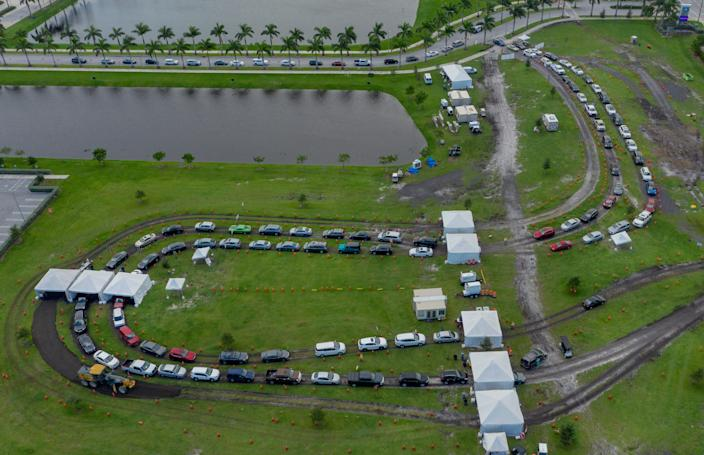 People wait in their cars to be tested for the coronavirus with drive-up rapid testing at the FITTEAM Ballpark of the Palm Beaches in West Palm Beach, Fla., on Oct. 23, 2020.