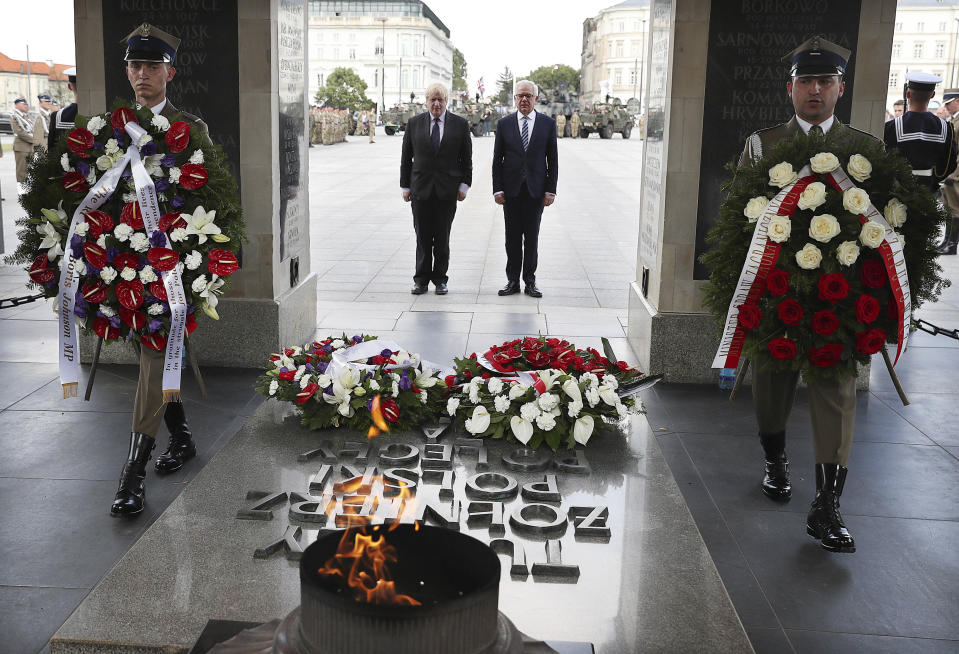 FILE - In this Thursday, June 21, 2018 file photo, Britain's Foreign Secretary Boris Johnson lays a wreath at the Tomb of the Unknown Soldier with his Polish counterpart Jacek Czaputowicz in Warsaw, Poland. Poland is reviving plans to reconstruct a historic Warsaw palace where the German Enigma machine codes were first cracked in 1932 and which Nazi German occupying forces blew up in 1944, it was announced Wednesday, July 7, 2021. The palace once housed a cipher office where the German Enigma encoding machine was first cracked. Only a colonnade that contains the Tomb of the Unknown Soldier still survives. Plans to have the palace rebuilt have been made ever since the war's end.(AP Photo/Czarek Sokolowski, file)