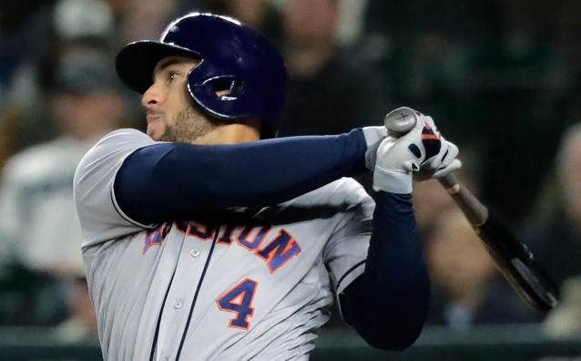 FILE - In this April 19, 2018, file photo, Houston Astros' George Springer takes a swing during a baseball game against the Seattle Mariners in Seattle. Springer is using a bat made by Axe Bat, a company headquartered in Renton, Wash., that is trying to revolutionize baseball with a simple concept -- a bat handle that is shaped like the handle of an axe. (AP Photo/Ted S. Warren, file)
