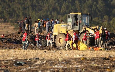 <span>Members of the search and rescue mission carry dead bodies at the scene of the Ethiopian Airlines Flight ET 302 plane crash, near the town of Bishoftu</span> <span>Credit: Reuters </span>