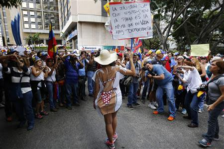 An anti-government protester holds up a sign as she poses for photographers during a march in Caracas