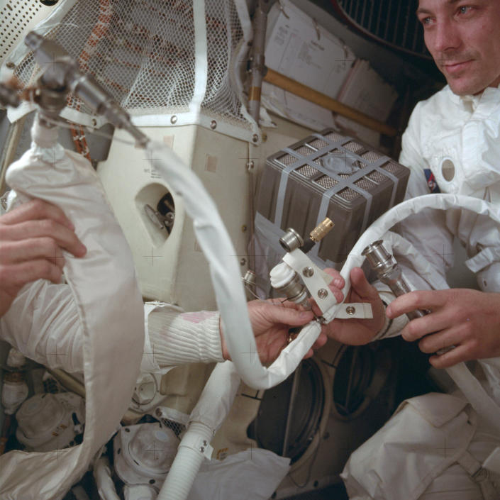 "In this April 1970 photo provided by NASA, Apollo 13 command module pilot John Swigert helps to hook up a lithium hydroxide canister in the lunar module, in an effort to get rid of carbon dioxide in the cabin as the spacecraft attempts to return to Earth. The explosion of an oxygen tank in the service module forced the three-man crew to rely on the lunar module as a ""lifeboat."" (NASA via AP)"