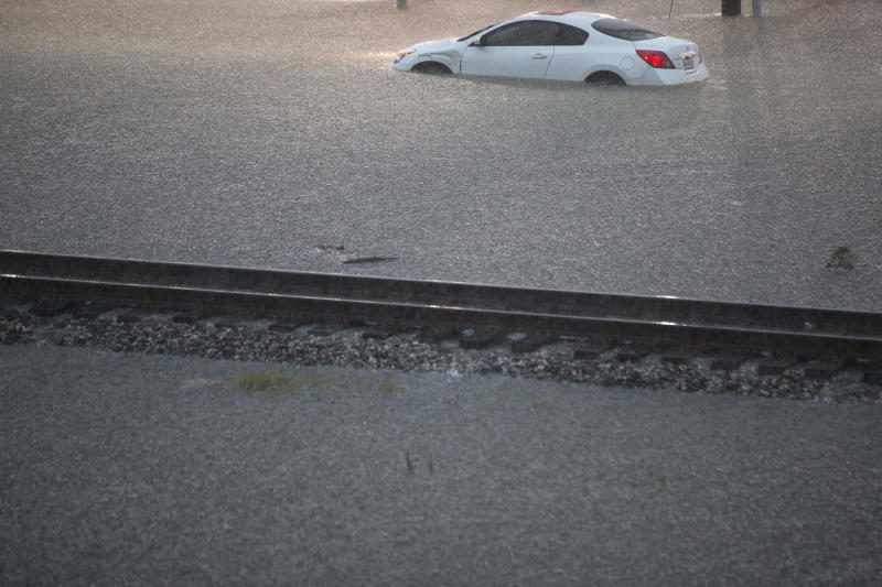 A flooded out car is stranded in high water off U.S. 59 as rain from Tropical Depression Imelda inundated the area on Sept. 19, 2019, near Spendora, Texas. (Photo: Brett Coomer/Houston Chronicle via AP)