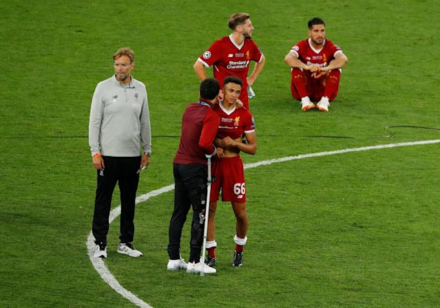 Soccer Football - Champions League Final - Real Madrid v Liverpool - NSC Olympic Stadium, Kiev, Ukraine - May 26, 2018 Liverpool's Trent Alexander-Arnold looks dejected with manager Juergen Klopp and team mates after losing the Champions League final REUTERS/Phil Noble