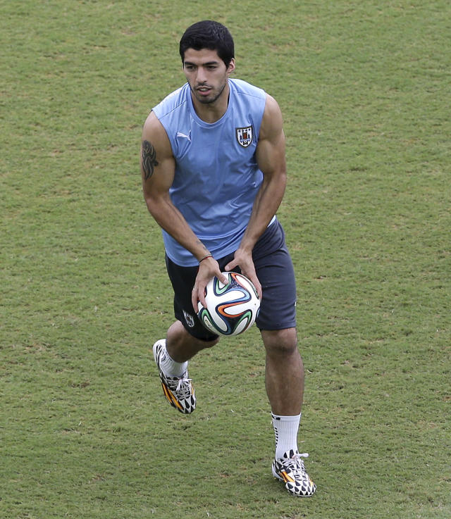 Uruguay's Luis Suarez runs on the pitch with a ball, during a training session the day before the team's next group D World Cup soccer match, at the Arena das Dunas in Natal, Brazil, Monday, June 23, 2014. (AP Photo/Antonio Clanni)