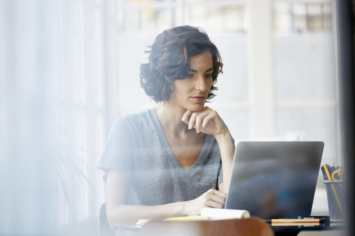 Beautiful young businesswoman with hand on chin using laptop in office