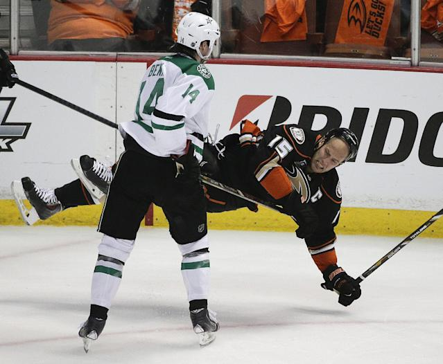 Dallas Stars' Jamie Benn(14) checks Anaheim Ducks' Ryan Getzlaf during the first period in Game 1 of the first-round NHL hockey Stanley Cup playoff series on Wednesday, April 16, 2014, in Anaheim, Calif. (AP Photo/Jae C. Hong)