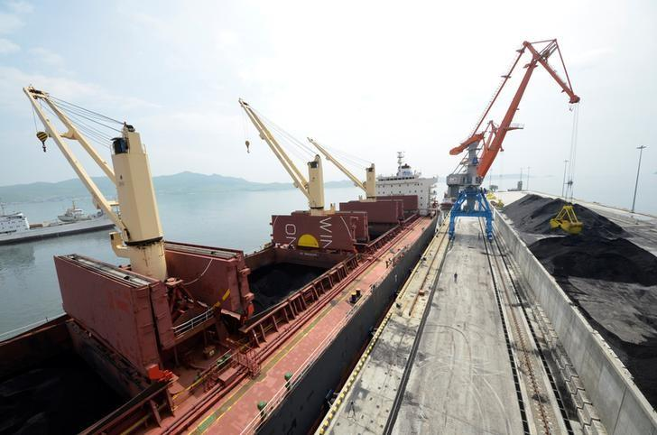 A cargo ship is loaded with coal during the opening ceremony of a new dock at the North Korean port of Rajin
