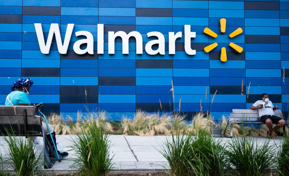 People wearing facemasks sit outside a Walmart store in Washington, DC on July 15, 2020. - Walmart will require shoppers to wear face masks starting next week, the US retail giant announced on July 15, joining an increasing number of businesses in mandating the protection amid the latest spike in coronavirus cases. (Photo by ANDREW CABALLERO-REYNOLDS / AFP) (Photo by ANDREW CABALLERO-REYNOLDS/AFP via Getty Images)