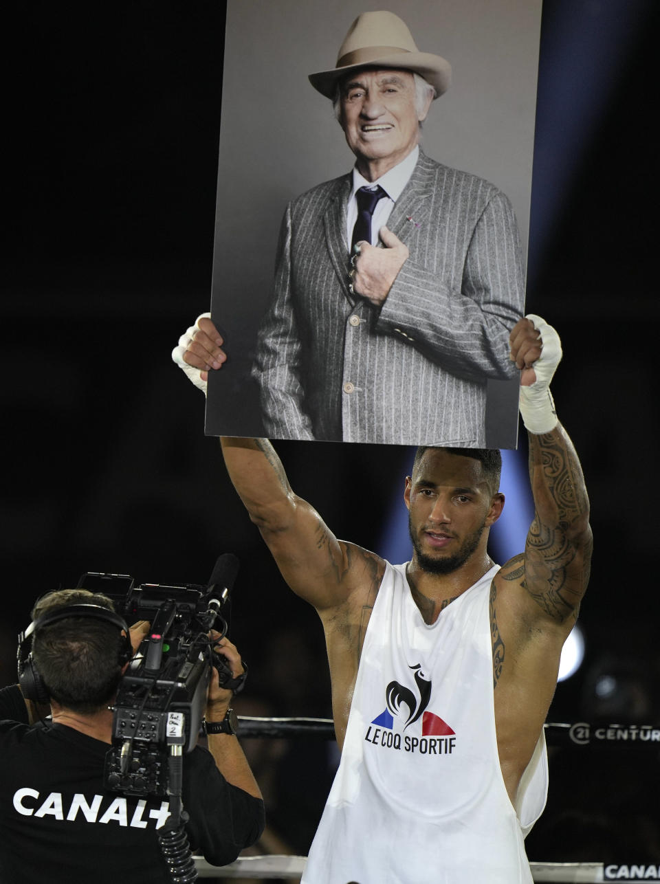 Tony Yoka of France holds up a photo of late French actor Jean-Paul Belmondo after he defeated Croatia's Petar Milas in a heavyweight boxing fight on the central court Philippe Chatrier at the Roland Garros tennis stadium, in Paris, Friday, Sept. 10, 2021. Belmondo a boxing enthusiast and former amateur boxer died earlier this week aged 88 (AP Photo/Francois Mori)