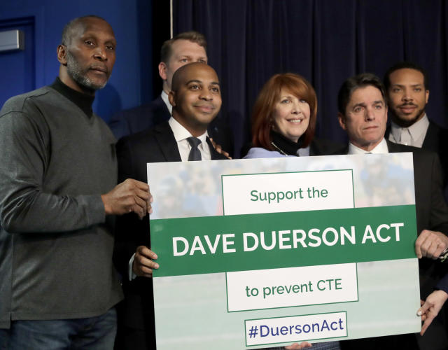 Tregg Duerson, and Carol Sente are surrounded by supporters of a bill banning football for young Illinois children. (AP)
