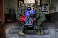 Soldiers carry a woman on a wheelchair at a Santiago polling station during the constitutional referendum vote