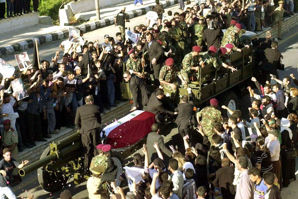 FILE - In this June 13, 2000 file photo, hundreds chant slogans as the coffin of the late Syrian President Hafez Assad, is brought to a mosque in Qardaha, Syria. On Nov. 13, 1970, Hafez Assad a young career air force officer launched a bloodless coup. Fifty years later, Hafez Assad's family still rules Syria. The country is in ruins from a decade of civil war that killed around a half million people, displaced half the population and virtually wiped out the economy. But Hafez's son, Bashar Assad, has an unquestioned grip on what remains. (AP Photo/Martin Gnedt, File)