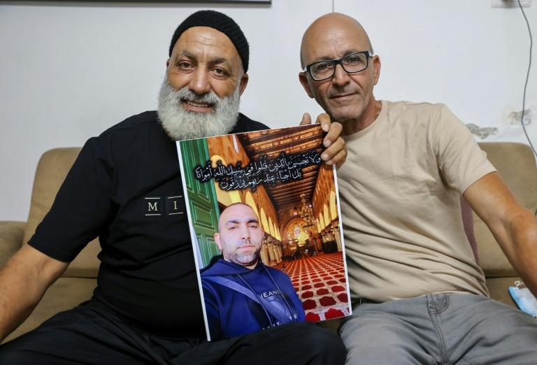 Malek Hassuna, on the left, holds a picture of his son Mussa, who was shot dead by Jewish vigilantes. He sits with Effi Yehoshua, whose brother was also killed (AFP/AHMAD GHARABLI)