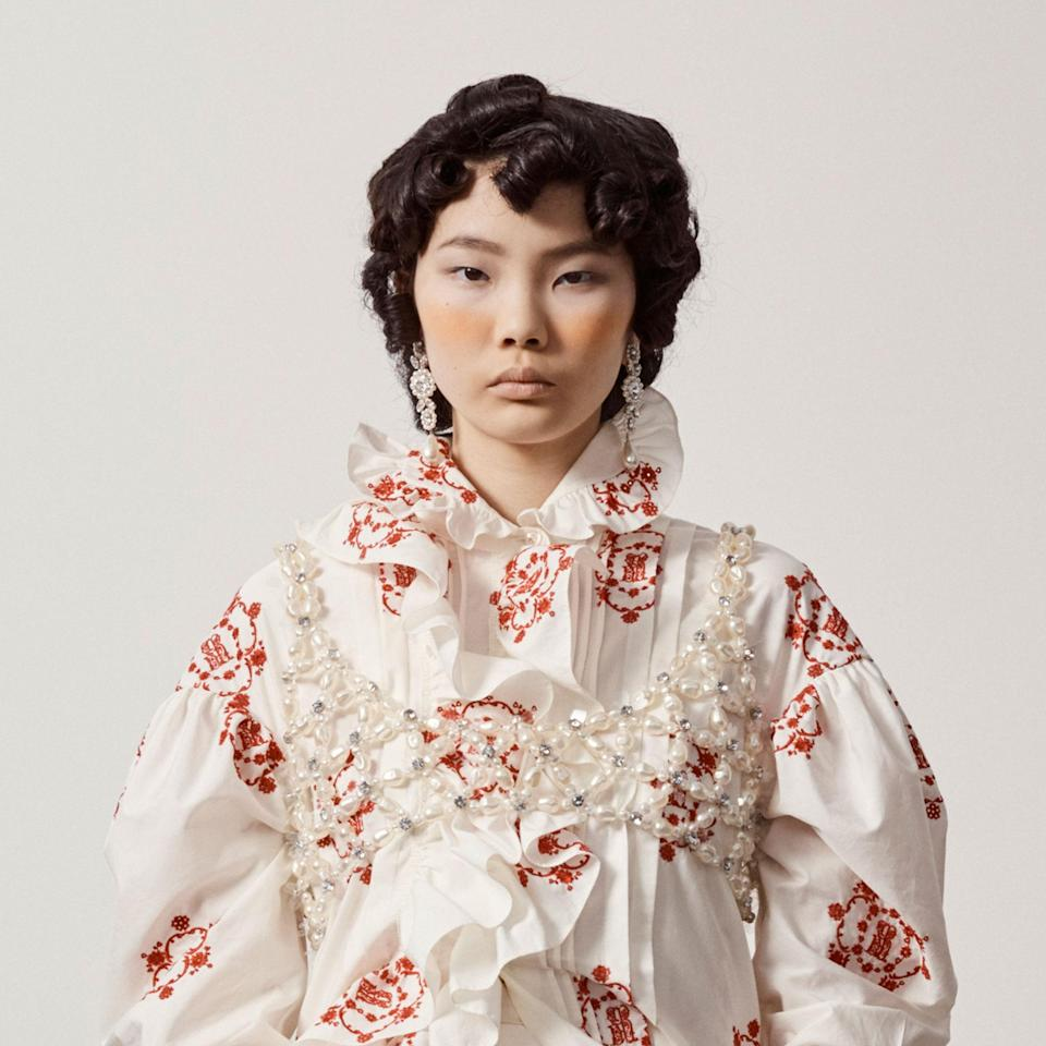 """The tight, Victorian-style ringlets on the models at Simone Rocha were created by hairstylist <a href=""""https://www.instagram.com/cyndiaharvey/"""" rel=""""nofollow noopener"""" target=""""_blank"""" data-ylk=""""slk:Cyndia Harvey"""" class=""""link rapid-noclick-resp"""">Cyndia Harvey</a> with tiny curling irons. To further the period film vibes, makeup artist Thomas de Kluyver swept peachy pigments onto cheeks, which dramatically contrasted the model's matte skin and creamy nude lips."""