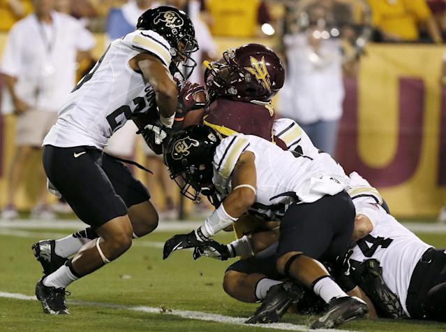 Arizona State's Marion Grice scores a touchdown as he takes Colorado's Greg Henderson, left, Jered Bell, second from right, and Addison Gillam, right, into the end zone during the first half of an NCAA college football game on Saturday Oct. 12, 2013, in Tempe, Ariz. (AP Photo/Ross D. Franklin)