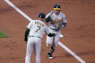 Oakland Athletics' Ramon Laureano (22) is congratulated by third base coach Mark Kotsay as he jogs home on a solo home run off Minnesota Twins pitcher Matt Shoemaker during the third inning of a baseball game Friday, May 14, 2021, in Minneapolis. (AP Photo/Jim Mone)