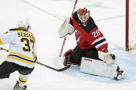 New Jersey Devils goaltender Mackenzie Blackwood (29) makes a glove save with Boston Bruins center Patrice Bergeron (37) threatening in front of the crease during the first period of an NHL hockey game, Tuesday, May 4, 2021, in Newark, N.J. (AP Photo/Kathy Willens)