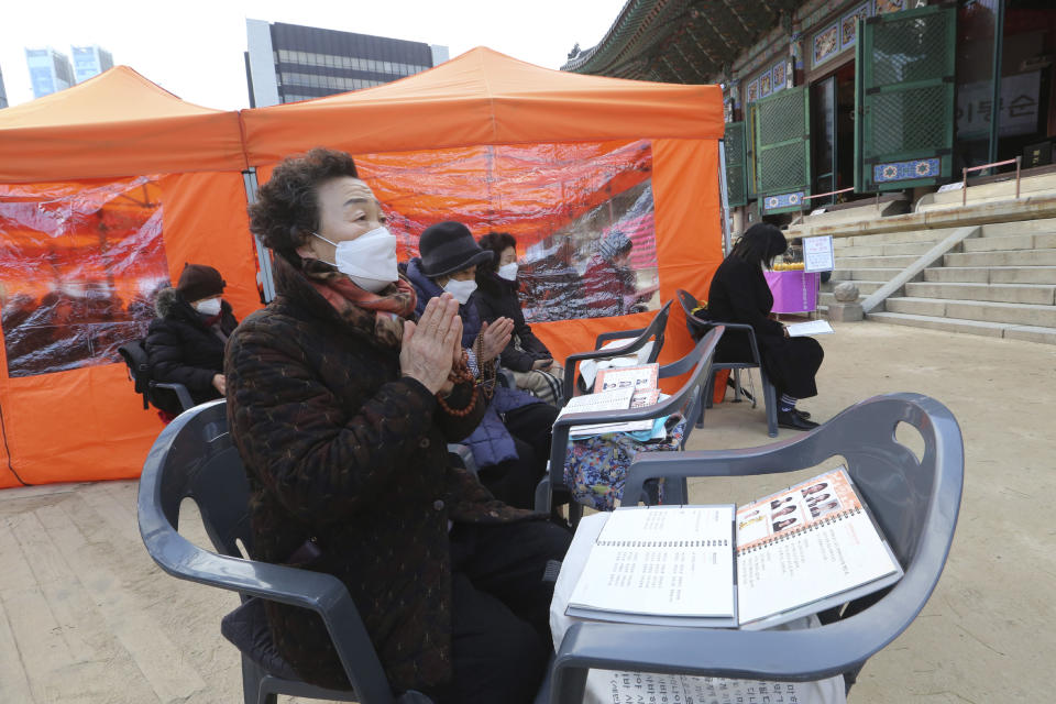 Parents wearing face masks as a precaution against the coronavirus pray during a special service to wish for their children's success in the upcoming college entrance exam on Thursday, Dec. 3, at the Jogye Temple in Seoul, South Korea, Sunday, Nov. 29, 2020. South Korea is shutting down indoor gyms offering intense workout classes and banning year-end parties at hotels in the greater Seoul area to fight the virus. Prime Minister Chung Sye-kyun said Sunday. (AP Photo/Ahn Young-joon)